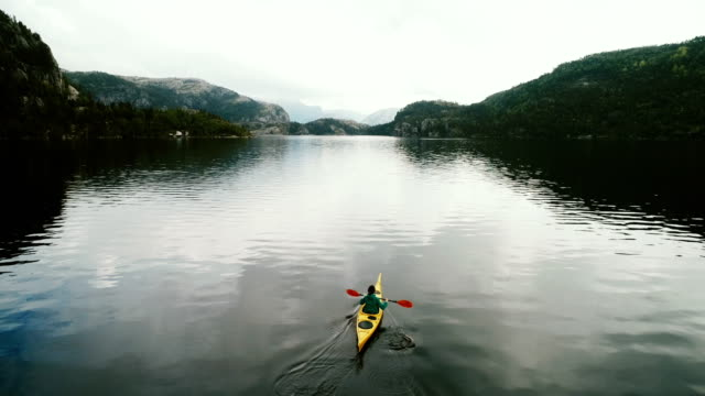 Aerial view of woman kayaking on the lake in mountains video