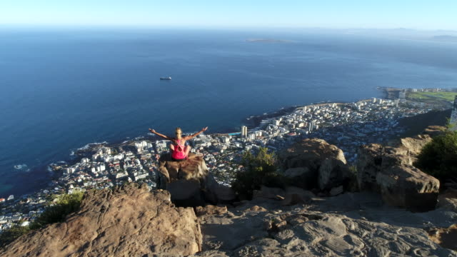 Aerial view of woman reaching mountain top Aerial view of a young woman reaching the top of Lion's head mountain in Cape Town, South Africa. table mountain national park stock videos & royalty-free footage