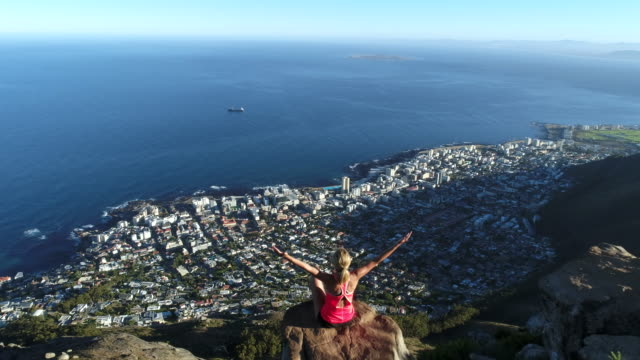 Aerial view of woman reaching mountain top Aerial view of a young woman reaching the top of Lion's head mountain in Cape Town, South Africa. western cape province stock videos & royalty-free footage