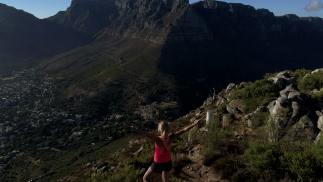 Aerial view of woman reaching mountain top Aerial view of a young woman reaching the top of Lion's head mountain in Cape Town, South Africa. cape peninsula stock videos & royalty-free footage