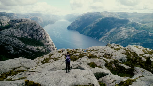 Aerial view of woman walking and  looking at Lysefjorden from Preikestolen video
