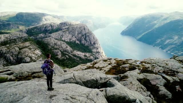 vídeos de stock e filmes b-roll de aerial view of woman walking and  looking at lysefjorden from preikestolen - noruega
