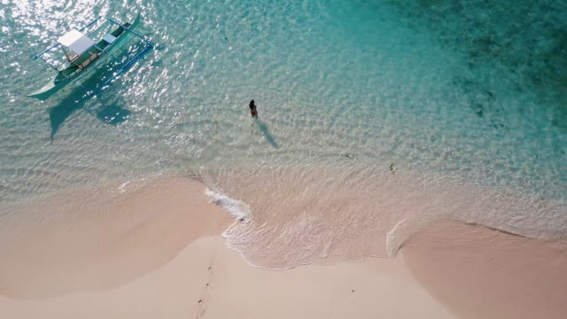 aerial (drone) view of woman walking into ocean - purezza video stock e b–roll