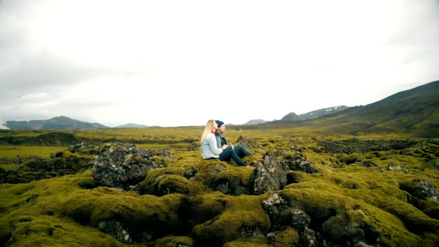 Aerial view of young beautiful couple sitting and enjoying the landscape of lava field in Iceland. Copter flying around video