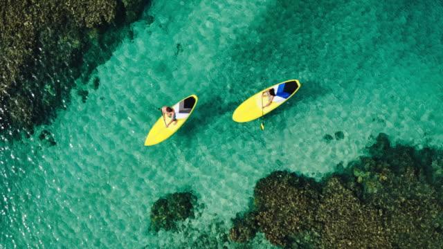 vídeos de stock, filmes e b-roll de vista aérea do jovem casal de pé para crianças - equipamento de esporte aquático