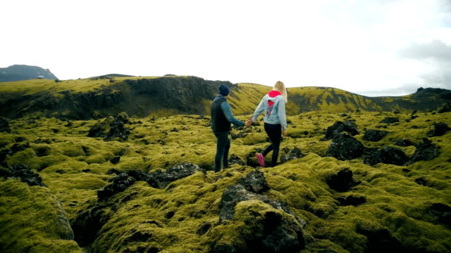 Aerial view of young couple walking on the volcanic lava field in Iceland. Man and woman enjoying the landscape