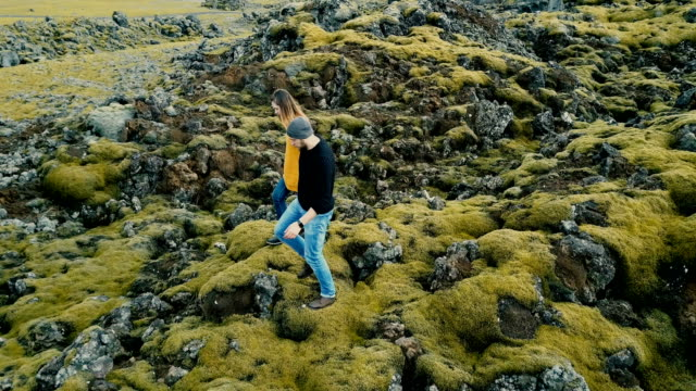 Aerial view of young stylish couple walking through the volcanic lava field in Iceland. Man and woman go to their car video