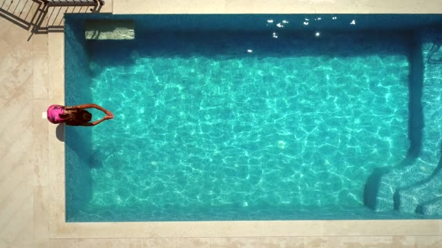 vídeos de stock e filmes b-roll de aerial view of young woman diving into swimming pool. - jump pool, swimmer