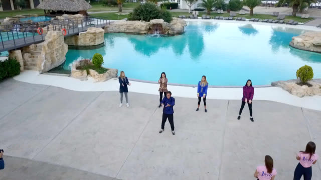 Aerial view of young women doing tai chi by the pool