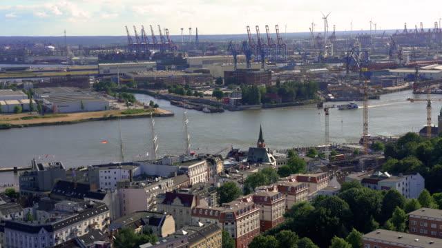 ハンブルクの貨物ターミナルでのハンブルク市とコンテナ船の空中写真 ビデオ
