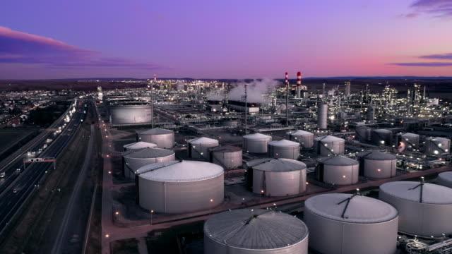 ws aerial view oil refinery and freeway at dusk - gaz filmów i materiałów b-roll