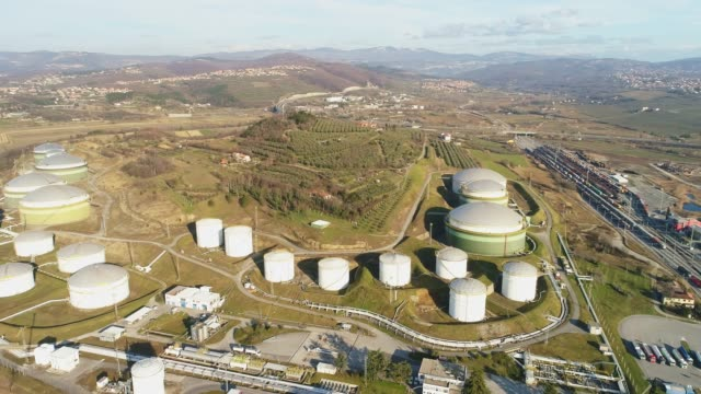 Aerial view oil storage tanks among sunny landscape,Slovenia Aerial view oil storage tanks among sunny landscape,Slovenia. WS,real time. storage tank stock videos & royalty-free footage