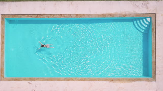 aerial view on a woman swimming in a private villa pool - вилла стоковые видео и кадры b-roll