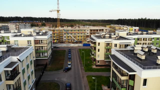 Aerial view on buildings under construction, crane with cargo Aerial view on buildings under construction, crane with cargo. Fligh over rooftops of modern housing estate. complexity stock videos & royalty-free footage