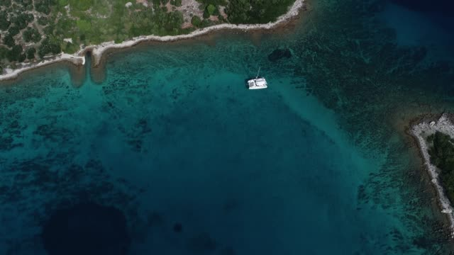 地中海の小さな島の近くに停泊の双胴船の空中写真 ビデオ