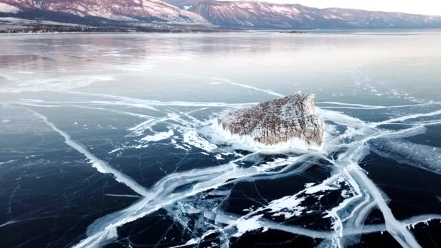 vídeos de stock e filmes b-roll de aerial view on lake baikal. winter lake with beautiful ice. rocks on the coast and islands. russian winter. drone shot. - lago baikal