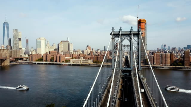 Aerial view on Manhattan bridge in New York, America. Drone flying over the East river, boat riding through video