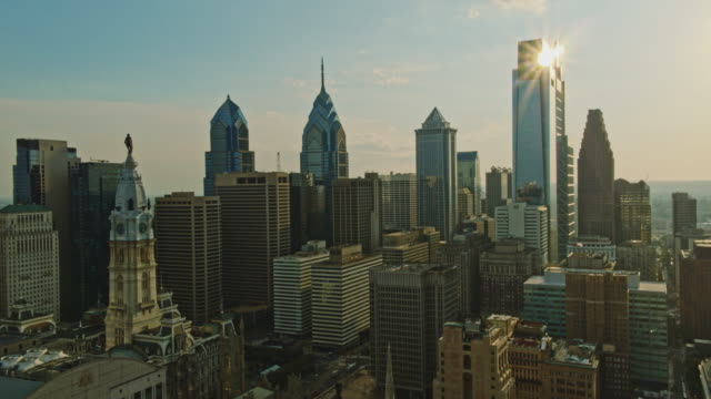 Aerial view on Philadelphia City Hall in front of Downtown District, Philadelphia, Pennsylvania, at sunset.  Drone video with the cinematic forward and wide panoramic-orbiting camera motion.