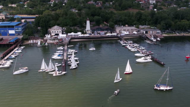 Aerial view on sail boats float on the sea. Calm sea and sail boats by the pier. Yachts and boats video