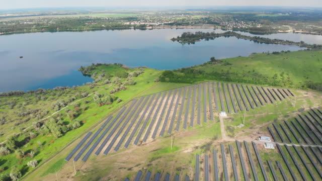 vídeos de stock, filmes e b-roll de vista aérea sobre solar usina em green field perto do rio no dia ensolarado - multicóptero