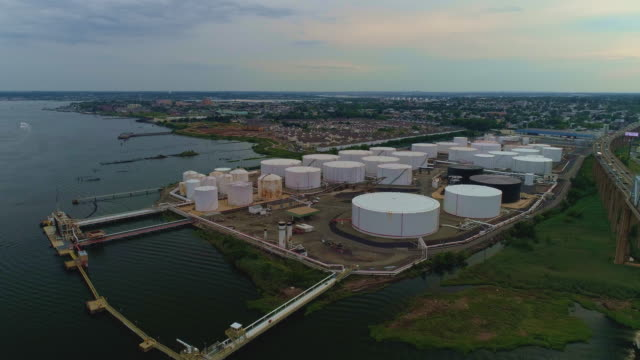 Aerial view on the oil storage tanks at a petroleum terminal over the Outerbridge Crossing bridge, in New Jersey at the border with the New York State on the Arthur Kill tidal strait shore.