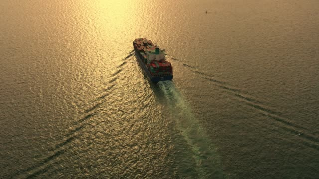 Aerial view on the top of the cargo ship carrying out export and import business, logistics and sea transportation at sunset time video