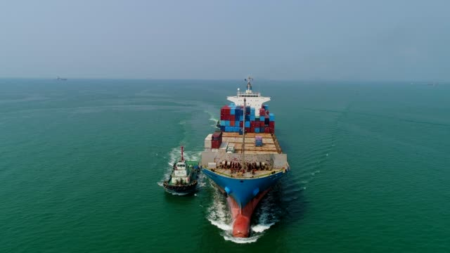 Aerial view or front view tugboat drag container ship from sea port driving on the sea for logistic import export or transportation.