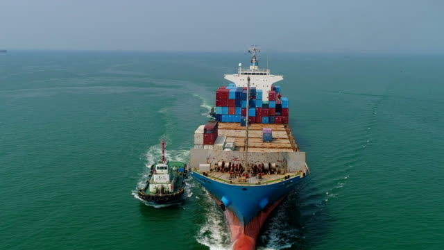 aerial view or front view tugboat drag container ship from sea port driving on the sea for logistic import export or transportation. - rimorchiatore video stock e b–roll