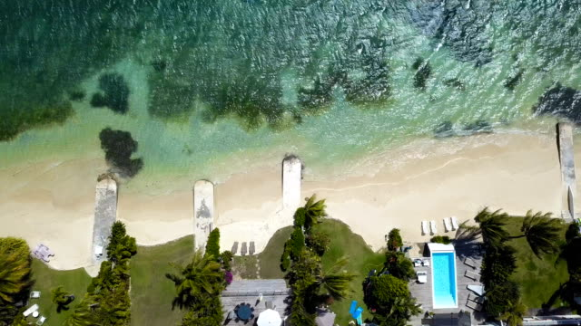 Aerial view over a beach in a lagoon, in Guadeloupe. There is a turquoise water and villa on the beach, under the sun.