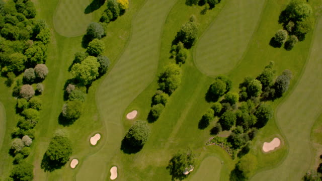 luftaufnahme über ein wunderschöner golfplatz in sonnenschein. 4k - golf stock-videos und b-roll-filmmaterial
