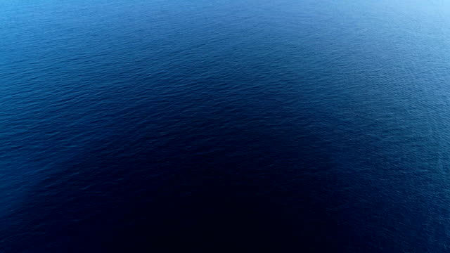 Aerial view over a boat at sea leaving a wake in Mediterranean Sea, with the reflection of the sun in blue water Sea. View over the blue water in the Mediterranean Sea.The water is dark blue with the reflection of the sun in it. There is only water and the sky in the horizon. dark blue stock videos & royalty-free footage