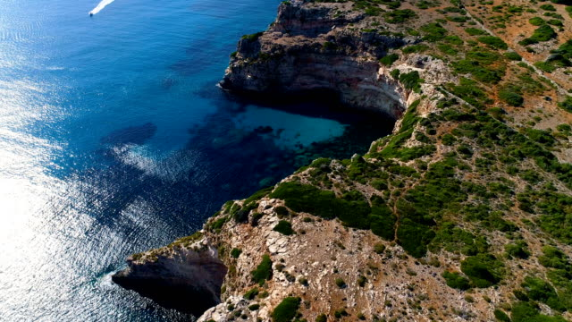 aerial view over a boat in mediterranean sea, with the reflection of the sun in blue water sea. the boat is sailing close to a cliff, under the sun. - mar mediterraneo video stock e b–roll