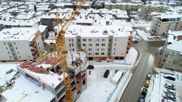 aerial view over a building construction site, panning shot, high point of view, wintertime, construction crane, residential area, construction business, - osiedle mieszkaniowe filmów i materiałów b-roll