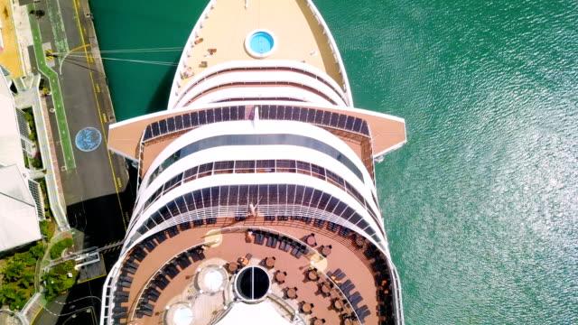 stockvideo's en b-roll-footage met luchtfoto over een cruiseschip boot op quay in guadeloupe onder de blauwe hemel. - cruise