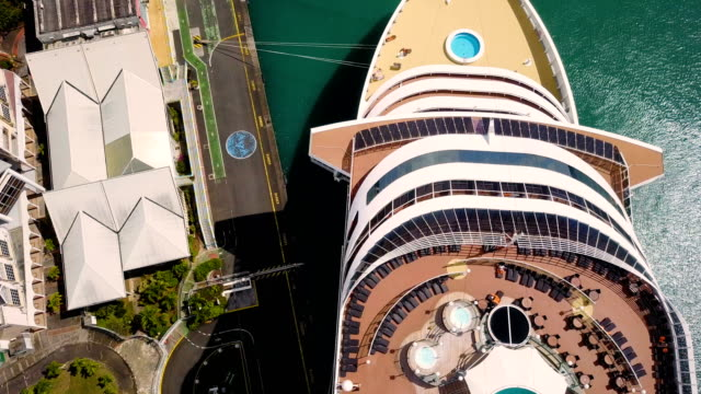 aerial view over a cruise liner boat at quay in guadeloupe under the blue sky. - cruise video stock e b–roll