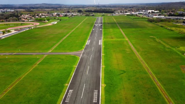 Aerial view over a landing runway with a drone which is going lower and lower in the on the runway. There is green grass around the empty airstrip without airplane, with a cloudy sky - 4K