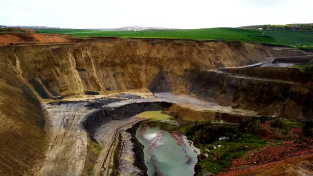 Aerial view over a mine in Morocco. We can see a giant hole because of the digging.