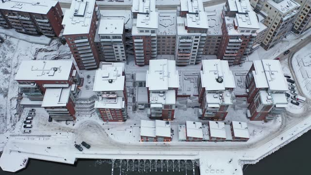 Aerial view over a residential area in winter Stationary view over a residential area with modern apartment buildings by the sea in winter in the Nacka municipality outside Stockholm, Sweden. ocean front properties stock videos & royalty-free footage