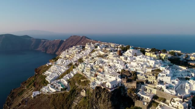 aerial view over a village on the top of a hill in santorini, under the blue sky. the city is near the mediterranean sea. - grecja filmów i materiałów b-roll