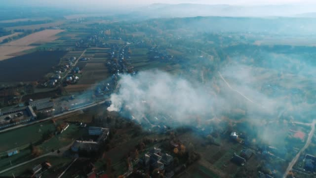 Aerial view over agricultural fields where farmers burn fires, doing seasonal work.