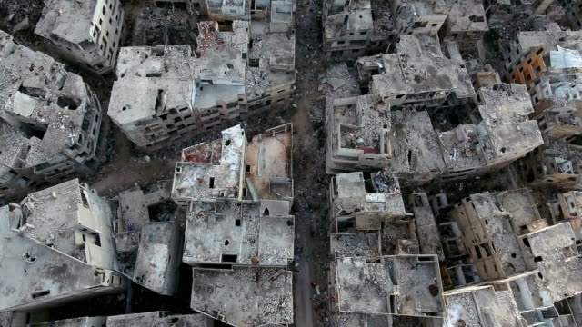 vídeos de stock e filmes b-roll de aerial view over damaged houses in aleppo. a city destroyed by bombing, only ruined houses left, under the blue sky. - síria
