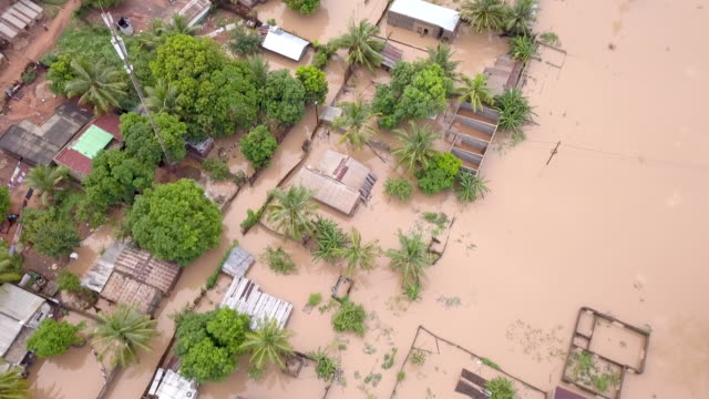 aerial view over flooded houses in village - climate change video stock e b–roll