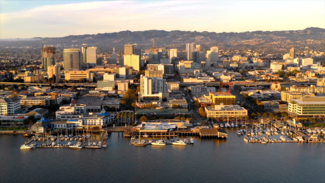 Aerial View Over Harbor and Waterfront Oakland California Late afternoon in Oakland California at the port waterfront across from Alameda oakland stock videos & royalty-free footage