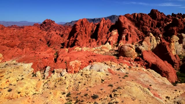 aerial view over red and white canyons and mountains in a desert landscape - red rock canyon national conservation area video stock e b–roll