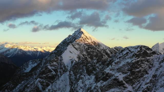 vídeos de stock e filmes b-roll de aerial view over snow covered high mountains at sunset - suíça