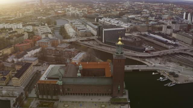 vídeos de stock, filmes e b-roll de vista aérea sobre a prefeitura de estocolmo-vídeo stock - sol nascente horizonte drone cidade