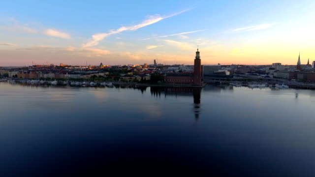 vídeos de stock, filmes e b-roll de vista aérea da prefeitura sobre estocolmo - sol nascente horizonte drone cidade