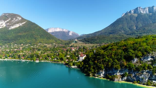 Aerial view over the blue Annecy Lake under blue sky - France. There is village between the Alps mountains in the background.