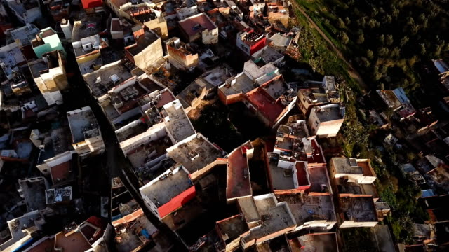 vídeos de stock e filmes b-roll de aerial view over the rooftops of moulay idriss in a valley in morocco, under the sun. - aldeia
