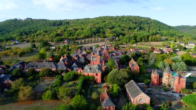 Aerial view over the village of Collonges-La-Rouge in France. The village is in the middle of a forest and green fields.